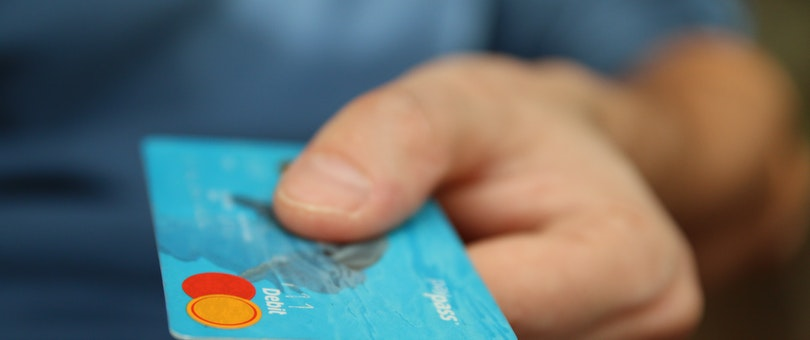person handing over a credit card for payment