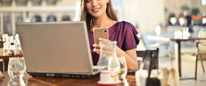 woman using her smartphone and laptop in a coffee shop