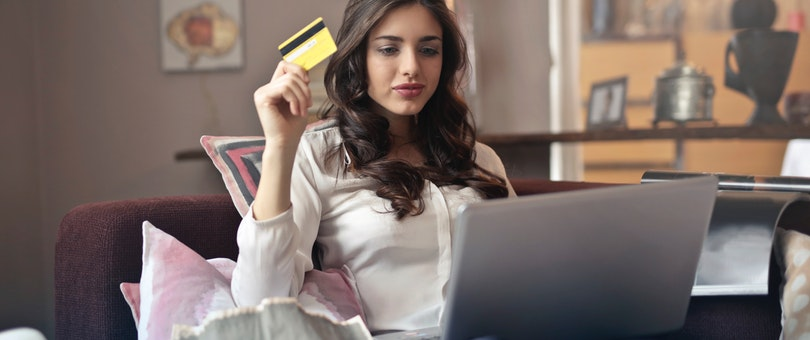 woman holding a yellow credit card while working on her laptop