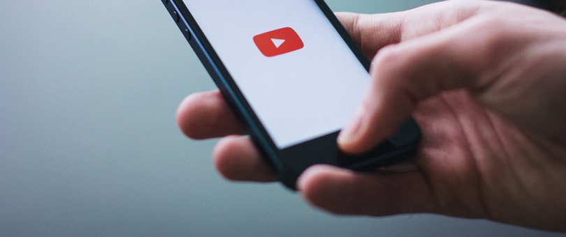 youtube logo on a smartphone held by a person