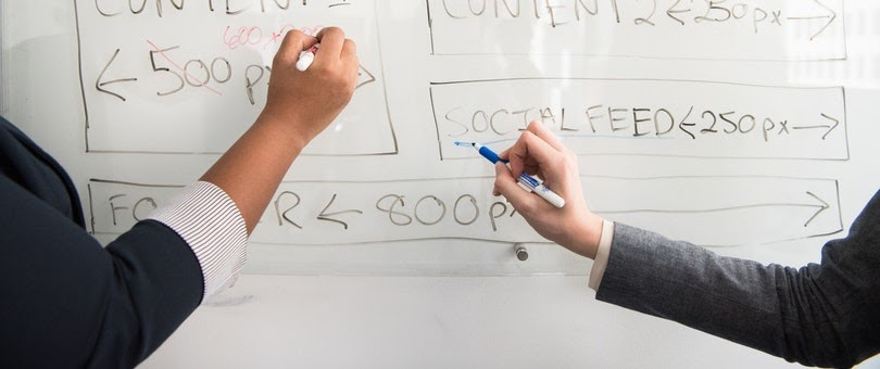 persons writing on whiteboard